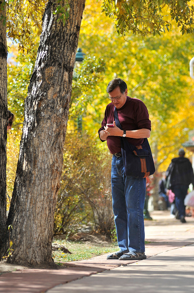 Walt Hester | Trail Gazette<br /> Duncan Case of Lincoln, Neb. checks his photo among the foliage olong the Riverwalk on Sunday. Visitors found colorful backdrops all over town this weekend.