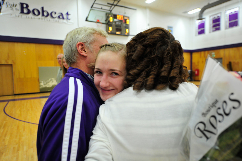 Walt Hester | Trail Gazette<br /> Senior volleyball player Stephanie Woolman seems a bit sheepish while receiving hugs from her parents at Senior Night on Tuesday. As the fall sports season winds down, soccer celebrated its seniors and the football team will have theri senior night in two weeks.