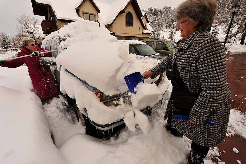 Walt Hester | Trail Gazette<br /> Marlene Baker, left, of Brush and Sharon Wolever of Snyder, Colo., use a mop and a dust pan to knock the 16 inches of snow off of their SUV along Elkhorn Avenue on Wednesday. While the big snow made for slow going in the morning, roads were merely wet by the afternoon in Estes Park.
