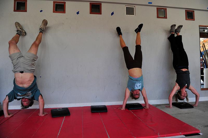 Walt Hester | Trail Gazette<br /> Garth and Cathy Lewis and Janelle Coop perform handstand push ups Last week. Their CrossFit workouts are designed to make them ready for anything.