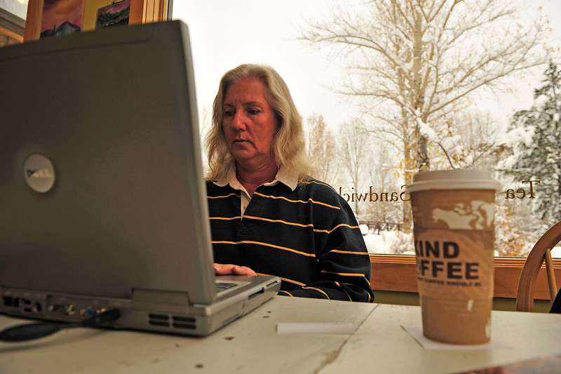 "Walt Hester | Trail Gazette<br /> Sue Painter of Pinewood Springs gets caught up on her laptop on a coffee shop in Estes Park on Wednesday after her home lost power. ""We'be been without electricity since midnight,"" said Painter."