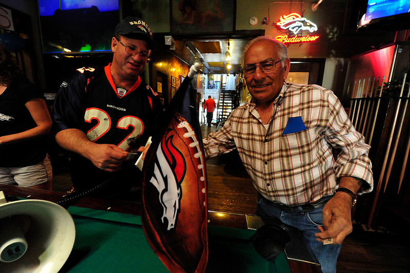 Walt Hester | Trail Gazette<br /> Gary Adler, the founder and president of the Pro Players Association, left, hands a Broncos car window flag to Joe Arguello on Sunday. On top of the Tebow jersey and the silent auction, smaller prizes were given away throughout the day.