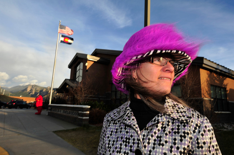 Estes Park Elementary School principal Karen Glassman stands out front of her school to greet students as strong winds blow her hat, hair and flag around on Tuesday. The wind was ahead of a weather system expected to bring between 4-15 inches of snow to the area.