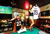 Walt Hester | Trail Gazette<br /> Gary Adler coaxes folks at the Wheel Bar on Sunday to enter the raffle for the Tim Tebow game jersey, held by Natalia Asher. The money will help the athletic programs of Estes Park schools.