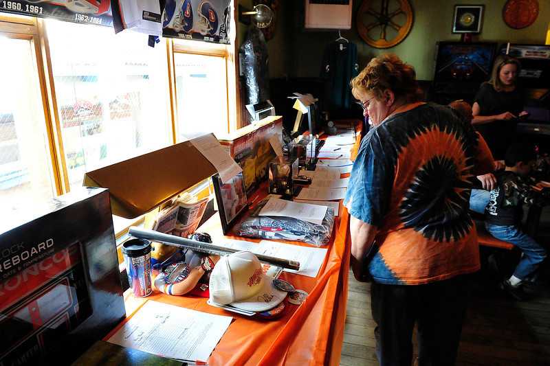 Walt Hester | Trail Gazette<br /> An attendee looks over the table of memorabilia and gifts for the silent auction on Sunday. All the money, again, went to support Estes Park athletic programs.