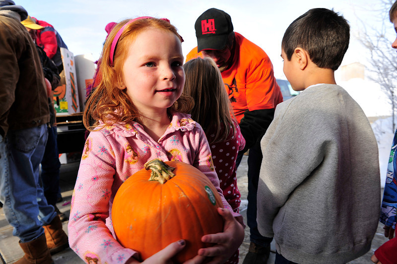 Walt Hester | Trail Gazette<br /> Elizabeth Michelle Miles hefts her pumpkin back into the Estes Park Elementary School on Thursday. The day was also Pajama Day at the school.