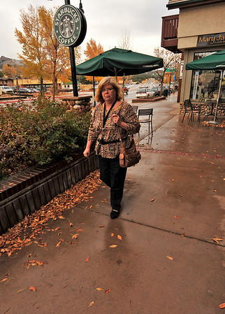 Walt Hester | Trail-Gazette<br /> Pat Leikawn of Manhattan, Kans. walks through damp leaves along Elkhorn Avenue on Friday.