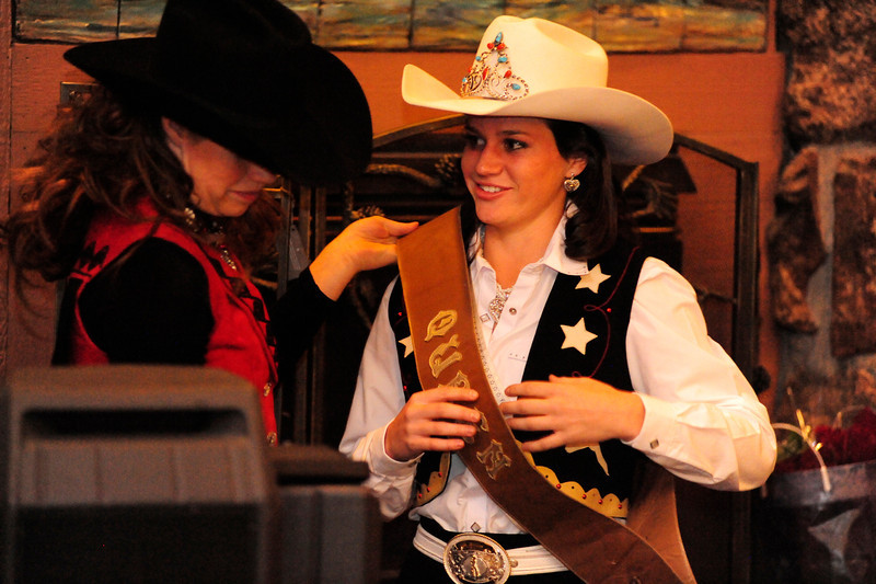 Walt Hester | Trail Gazette<br /> Kassi Fisher, 2011 Rooftop Rodeo Queen, hands over the sash and title on Thursday to Alex Hyland for 2012. Hyland will represent the Rooftop Rodeo for the next year