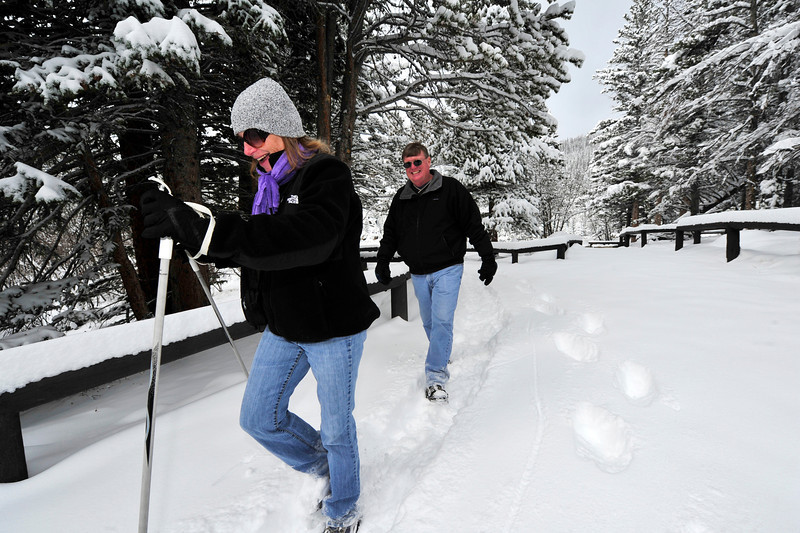 Walt Hester | Trail Gazette<br /> Lynda and Roger Hensing of Grinnell, Iowa, shuffle through new snow at Bear Lake on Wednesday. The new snow is encouraging winter outdoor enthuziasts to get started.