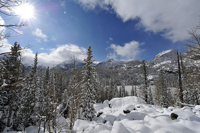 Walt Hester | Trail Gazette Clouds part and sunshine shimmers on new snow around Bear Lake on Wednesday. The fast-moving storm dumped another 9 inches of snow in the area that saw 17 last week.