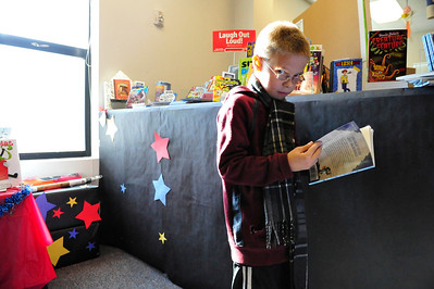 Walt Hester | Trail Gazette Mathew Laird, 10, of Estes Park looks up from his pick from the hundreds of choices at the elemetary school's Scholastic Book Fair on Friday. The Middle School's book fair is right around the corner.
