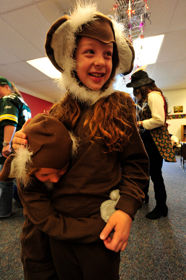 Walt Hester   Trail Gazette<br /> Isabel Gittings, 9, is hugged by her little sister, Evie, 4, during one of the elementary school's many classroom Halloween parties on Monday. Monkeies, football players, firefighters and soldiers as well as gouls and ghosts were all about the school.