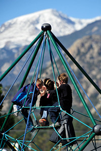 Walt Hester | Trail Gazette Children climb platground equipment at the Estes Park Elementary School on Monday. Temperatures were warm and pleasant on Monday while a change is expected, with lower temperatures and snow.