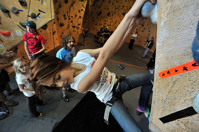 Walt Hester | Trail Gazette Harriett Fennell-McCrillis, 11, looks for a foot hold while family members watch. Rock climbing in Colorado has become a family activity with parents teaching children, who show siblings and friends.