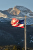 Walt Hester | Trail Gazette<br /> Longs Peak rises against a cloudles sky while a flag is lashed by wind at the Beaver Meadow entrance on Thursday. Friday should be mostly sunny with rain and snow possible on Saturday.