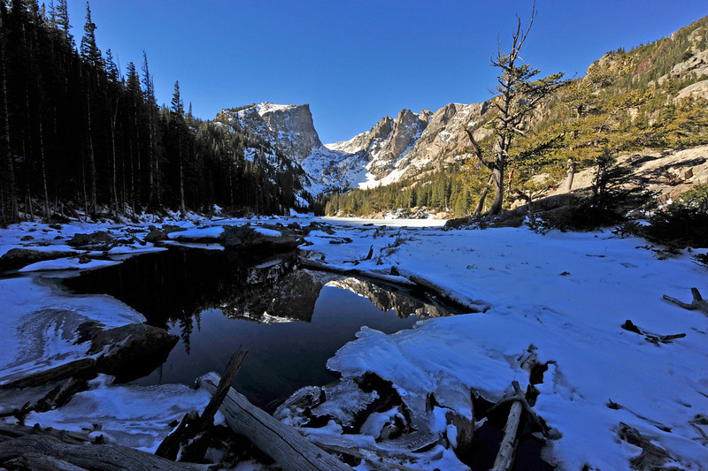 Walt Hester | Trail Gazette<br /> Hallett Peak reflects in an open spot in the ice on Dream Lake on Monday. The spots of open water are almost certain to ice over as a cold front moves into the area.