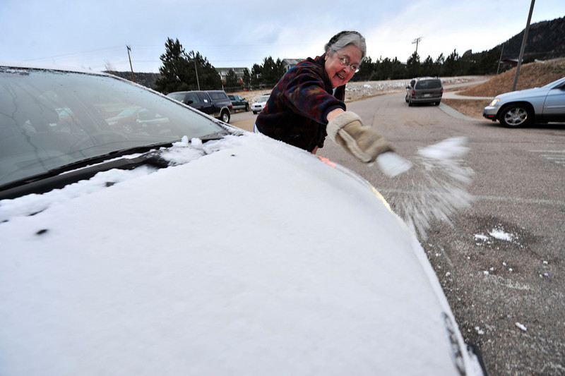 Walt Hester | Trail Gazette<br /> Toni Wilson of Estes Park scrapes snow and ice off of her car on Tuesday. While partly sunny skys are expected Friday, snow mat return for the weekend.