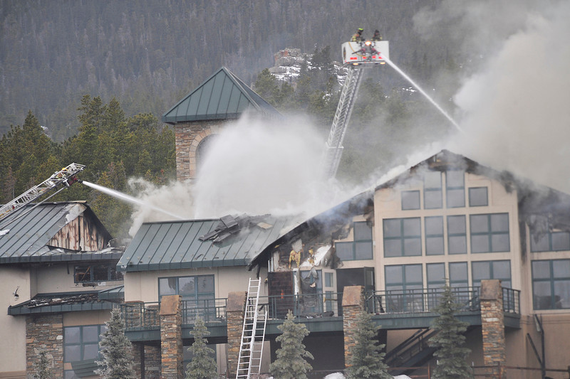 Walt Hester | Trail Gazette<br /> Firefigters spray the roof of the main lodge of the St. Malo Conference Center on Monday. Damage to the building included parcial roof collapse, but the fire did not spread into the trees or the guest lodging area.
