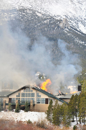 Walt Hester | Trail Gazette<br /> Wind-blone flames and smoke whip off of the roof of the main lodge of the St. Malo Retreat Center on Monday morning. High winds caused difficulties for firefighters who came from as far away as Big Elk Meadows to fight the blaze.
