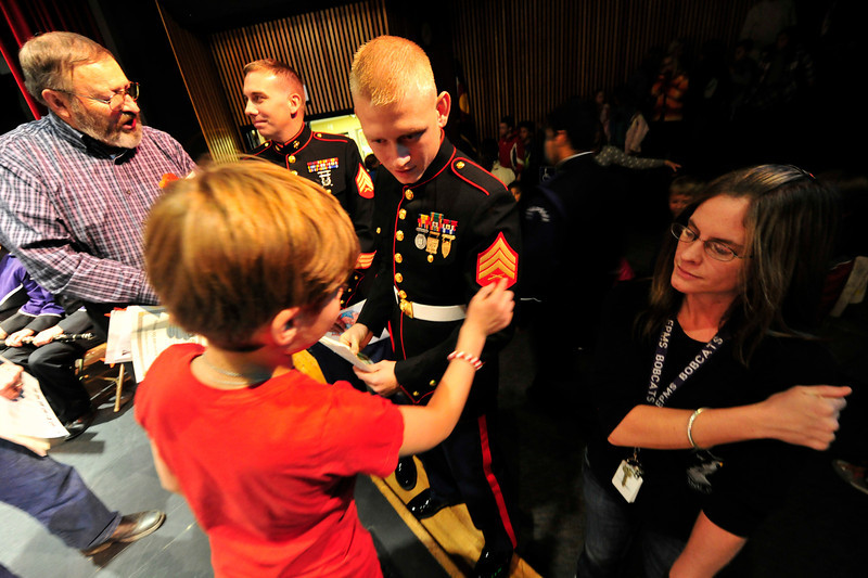 Walt Hester | Trail Gazette<br /> An elementary school student admires the sargent stripes of Marine Tyler Brown at the Veterans' Day program at the Estes Park High School auditorium on Friday. The district hopes to make the event a new tradition.