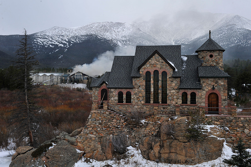 Walt Hester | Trail Gazette<br /> Smoke obscures Mount Meeker behind the iconic Chapel on the Rocks at the St. Malo Retreat and Conference Center on Monday. Firefighters from as far away as Berthoud and Lafayette were called to help battle the blaze south of Estes Park.