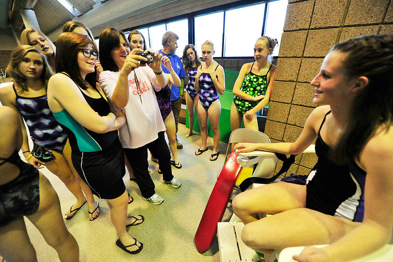 Walt Hester | Trail Gazette<br /> Mary Ann Quartetti snaps mug shots of her swimmers before practice on Wednesday. The first-season coach of the Ladycats had coached for 14 years before moving to Estes Park from Florida.