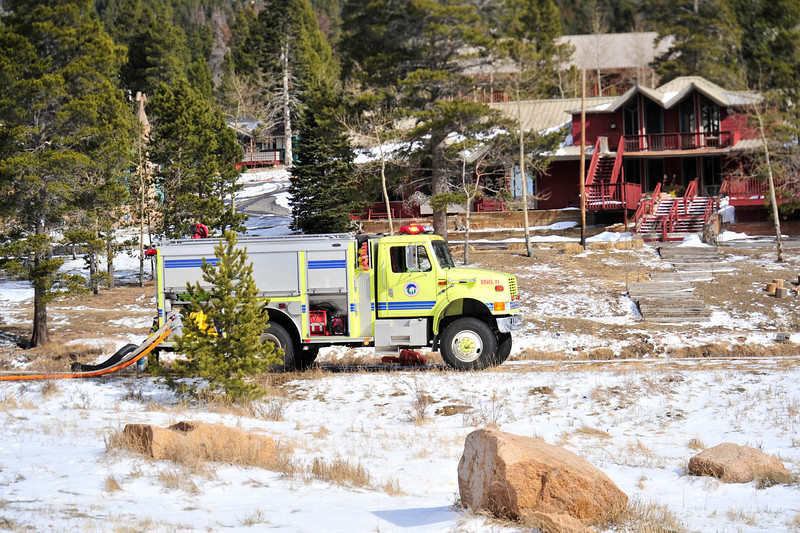 Walt Hester | Trail Gazette<br /> A truck from Allenspark pulls water out of the Aspen Lodge's pond to fight the fire at St. Malo, some three miles away. Firefighters had to scrmble to find a water source to fight the fire.