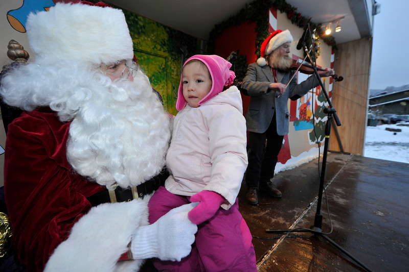Walt Hester | Trail Gazette<br /> Chloe Munkhsaikhan sits on Santa's lap in Bond Park on Saturday, while John Mueller entertains. Munkhsaikhan turns three on Christmas Day.