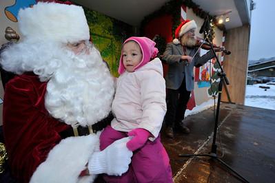 Walt Hester   Trail Gazette Chloe Munkhsaikhan sits on Santa's lap in Bond Park on Saturday, while John Mueller entertains. Munkhsaikhan turns three on Christmas Day.