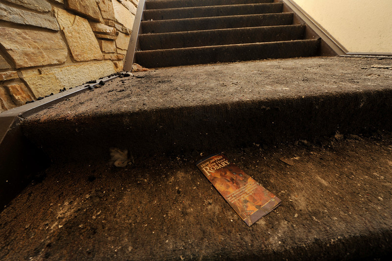 Walt Hester | Trail Gazette<br /> A brochure lies on a step amidst ashes and dirt at the St. Malo Retreat near Allenspark on Tuesday. Crews are cleaning up and shoring up the structure before engeneers determine how much of the structure can be saved.