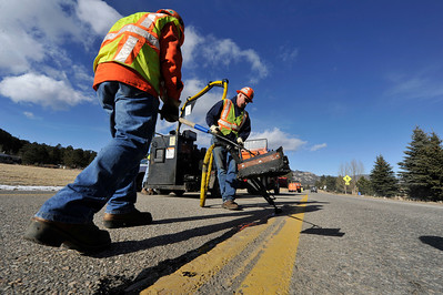 Walt Hester   Trail Gazette Mike McCleary, left, and Jim May of the Colorado Department of Transportation use the relatively warm and dry day to patch cracks on South St. Vrain Road on Tuesday. The tar they use keeps moisture out of the road, which might otherwise freeze and damage the road further.