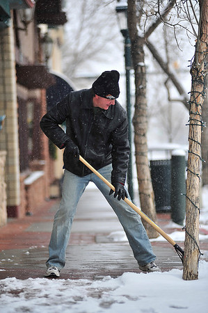 Walt Hester | Trail Gazette<br /> Kevin Schwery, owner of Main Street T's, clears th walkway infront of his shop on Thursday morning. The winter storm dropped about two inches on most of downtown, three inches elsewhere, but the cold temperatures and expected wind will cause more discomfort than the snow.