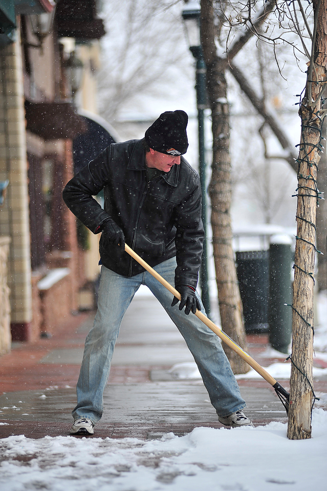 Walt Hester   Trail Gazette<br /> Kevin Schwery, owner of Main Street T's, clears th walkway infront of his shop on Thursday morning. The winter storm dropped about two inches on most of downtown, three inches elsewhere, but the cold temperatures and expected wind will cause more discomfort than the snow.