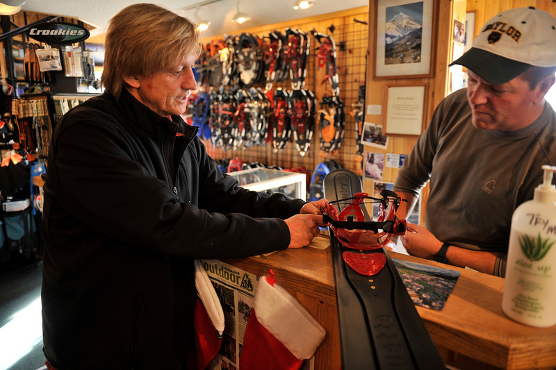 "Walt Hester | Trail Gazette<br /> Lake Thamm of Crecent Moon Snowshoes shows John Laughlin a prototype ""ski-able snowshoe"" with his company's snowshoe binding at the Warming Hut on Wednesday. Laughlin and the Warming House hope to carry the item if it goes into production."
