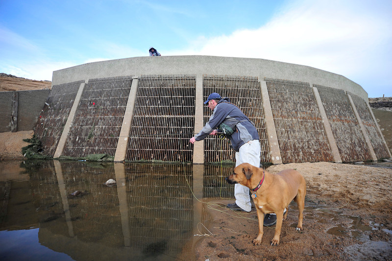 Walt Hester | Trail Gazette<br /> Glenn Barricklow of Fort Collins drags a line through a larger puddle in the drained Mary's Lake on Monday with the help of friends Neal Warner and Drake the dog, also of Fort Collins. The lake is drained periodically for maintenance on the dam and the tunnels in and out of the lake.