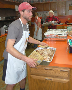 A dish of turkey is being moved from the oven to the serving area during Thursday's 11th annual Community Thanksgiving Feast. The annual event has grown to serve hundreds.