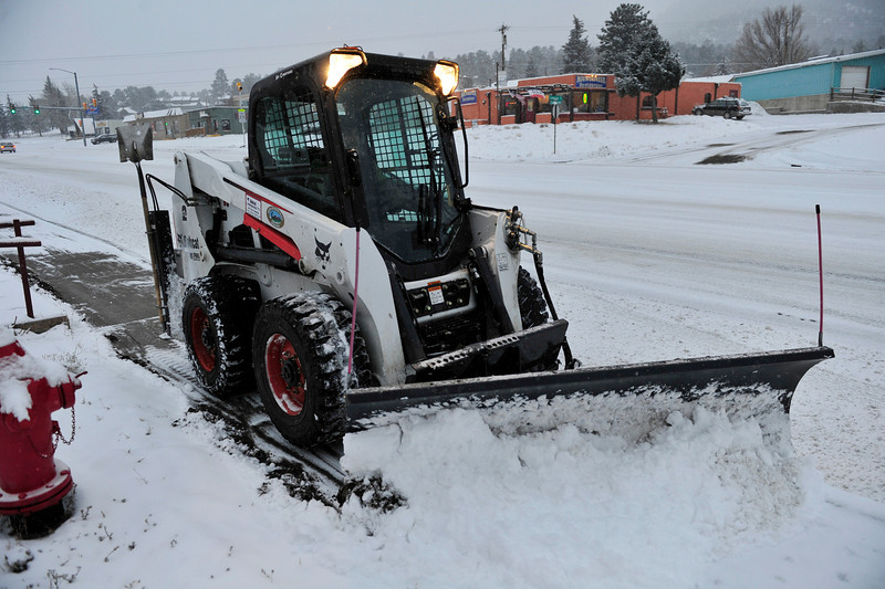 Walt Hester | Trail Gazette<br /> A town Bobcat pushes snow off of the sidewalk along South St. Vrain Avenue on Thursday morning. Town crews werte out early to clear streets and sidewalks of the new snow brought on by the latest winter storm.