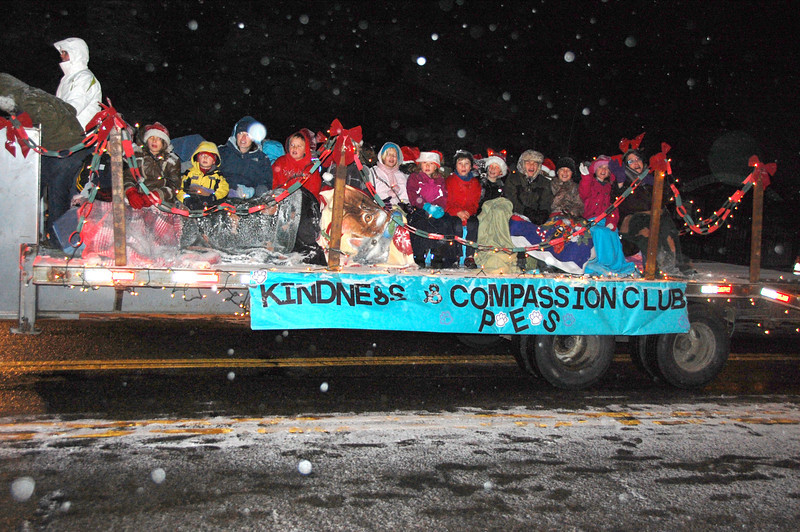 "Young people hunkered down on the ""Kindness and Comassion"" float in the 2011 Catch the Glow Christmas Parade."