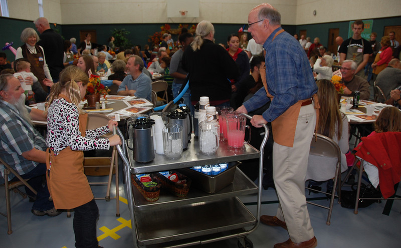 Volunteers move a drink cart through the tables Thursday during the 11th annual Community Thanksgiving Feast.