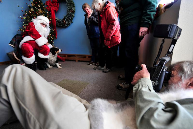 Walt Hester | Trail-Gazette<br /> Photographer Kent Dannen lies down to shoot Santa and an Australian sheepdog named Emily at the annual Pet Association event on Saturday.