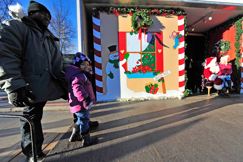 Walt Hester | Trail-Gazette<br /> Ava Bynum of Omaha, Nebr. smiles in anticipation while waiting to meet Santa with her dad, Vashon. Meeting Santa was one of many activities in Estes Park on Friday.