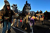 Walt Hester   Trail-Gazette<br /> Eight-year-old Madisyn Adas of Highlands Ranch smiles as she pets a Shire horse at the Town Hall as Audrey Stockton from Big Little Shires of LaPort, Colo. steadies the huge animals on Friday. Thousands of visitors were on hand to help Estes Park celebrate the start of the Holiday Season on Friday with wagon rides, a visit from Santa and the Catch the Glow Parade.