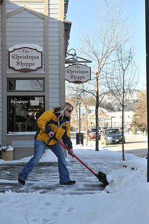 Walt Hester | Trail Gazette<br /> Elizabeth Dunnhardt shovels the walk along Elkhorn Avenue on Monday. More sunshine and less snow is in this week's forecast.