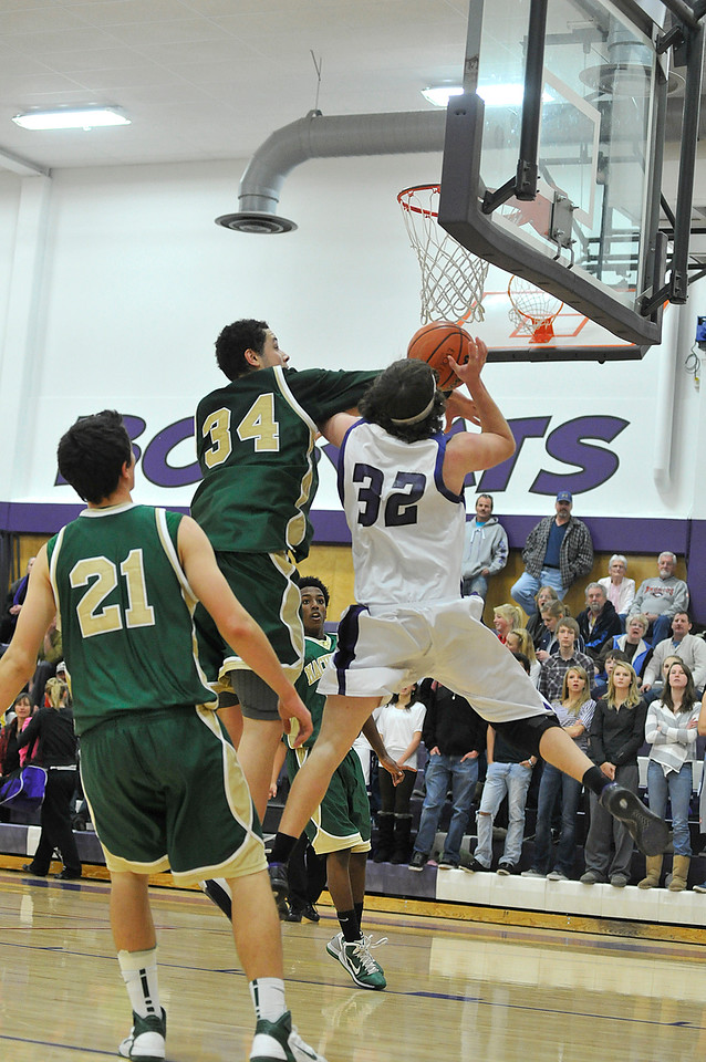 """Walt Hester   Trail Gazette<br /> Estes Park's Ty Holler, 32, takes a foul from Machebeuf forward Jordan Madrid-Andrews in the fourth quarter of their Saturday match up. Madrid-Andrews, at 6'6"""",  caused problems all over for the 'Cats."""