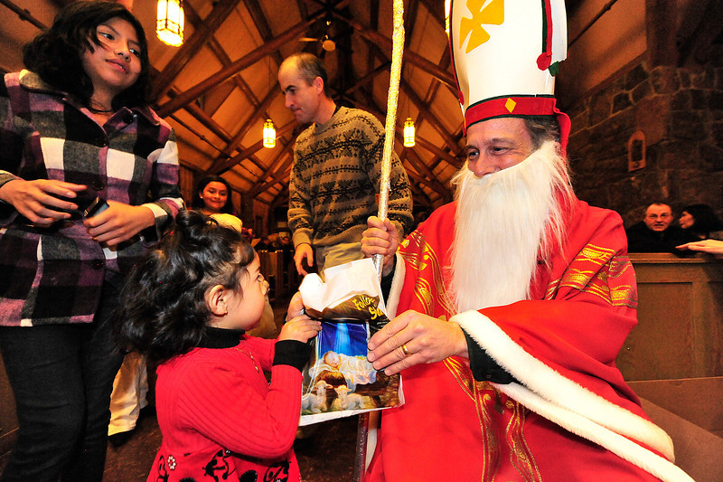 Walt Hester | Trail Gazette<br /> Saint Nicholas hands out gifts to children at the end of the pagent on Sunday. Legend has it that the famous saint and Catholic bishop snuck into homes at night to give money to the poor.