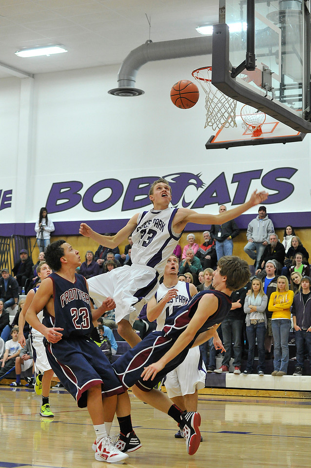Walt Hester   Trail Gazette<br /> Estes Park's Ben Cirone draws a blocking foul against Frontier Academy on Thursday. Ben finished with four points, two from freethrows in the final quarter, helping the Bobcats to their first home win, 64-48.