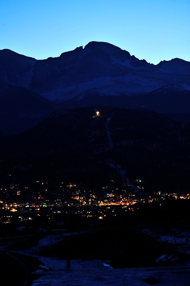 Walt Hester | Trail Gazette<br /> A lighted cross sits high on Prospect Mountain above the lights of Estes Park with Longs Peak looming beyond. A few private displays around Estes Park rival those found downtown.