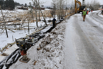 Walt Hester | Trail Gazette Crews work on the new multi-use trail through Monday's snow along Fish Creek Road. Officials want the trail finished before spring.