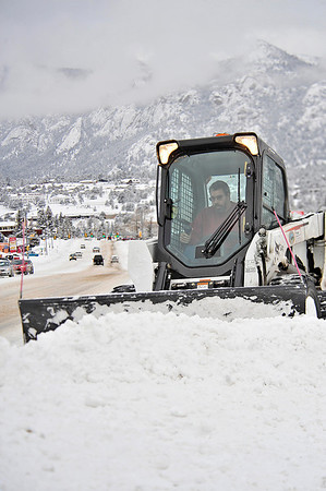 Walt Hester | Trail Gazette<br /> Chris Eshelman pushes snow off of the sidewalk along South St. Vrain Avenue on Thursday morning. Estes Park saw segnificant accumulation from the latest snow storm, though the Christmas weekend is expected to be dry and sunny.