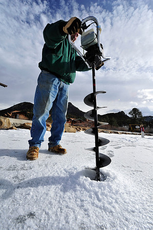 Walt Hester | Trail Gazette<br /> Lee Wicks of Trout Haven drills another hole in the ice on Wednesday. Trout Haven is offering ice skating on a newly constructed rink during the winter break, as well as ice fishing on their trout pond.